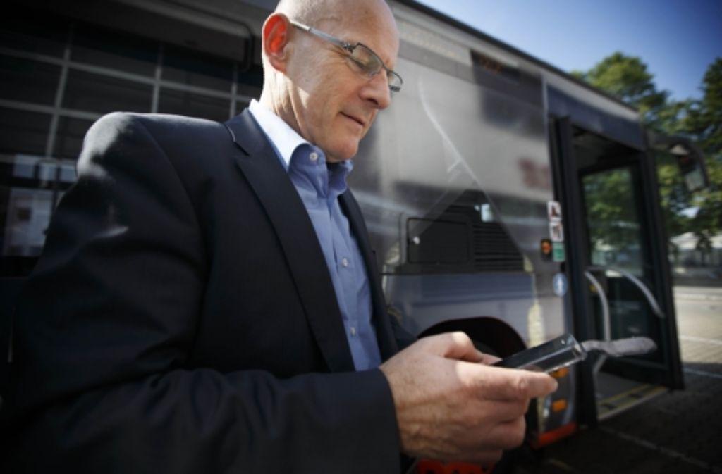 Verkehrsminister Winfried Hermann holt sich aktuelle Businformationen von seinem Handy. Foto: Gottfried Stoppel