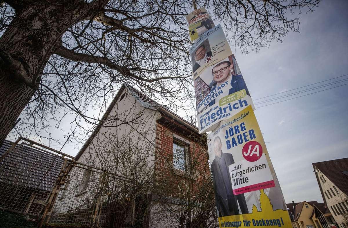 Wahlkampf bis fast auf die Spitze getrieben: Vier Backnanger OB-Kandidaten präsentieren sich an einer Laterne. Foto: Gottfried Stoppel