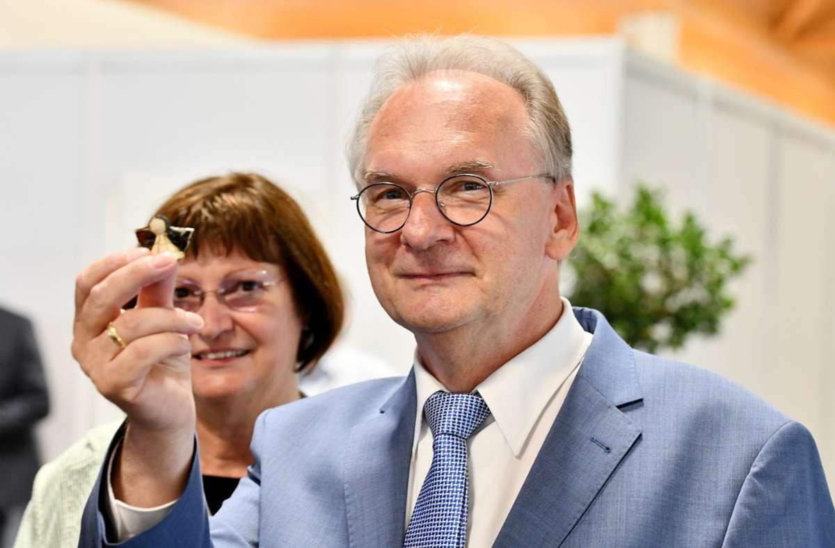 Reiner Haseloff hält einen Glücksbringer hoch: Er strebt eine dritte Amtszeit als Ministerpräsident an. Foto: dpa/Frank May