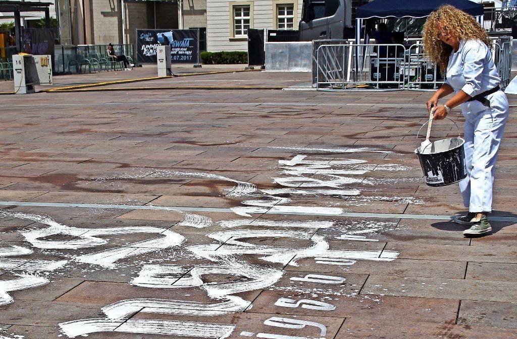 Die Kalligrafin Sigrid Artmann  malt den  Slogan vor das Rathaus. Foto: Dambacher-Schopf