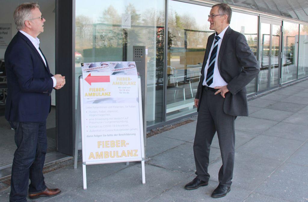 Mit Abstand begegnen sich der Klinik-Geschäftsführer Jörg Noetzel (links) und Landrat Roland Bernhard im Eingangsbereich des Böblinger Krankenhauses. Foto: Landratsamt