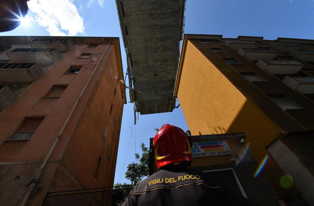 Ein Feuerwehrmann schaut auf die Überreste des Polcevera-Viadukt in Genua. Am 14. August 2018 stürzte um 11.30 Uhr  ein Teil der Brücke von etwa 250 Metern Länge rund um den westlichen Pylon ein. Dabei starben mindestens 40 Menschen. Foto: AP