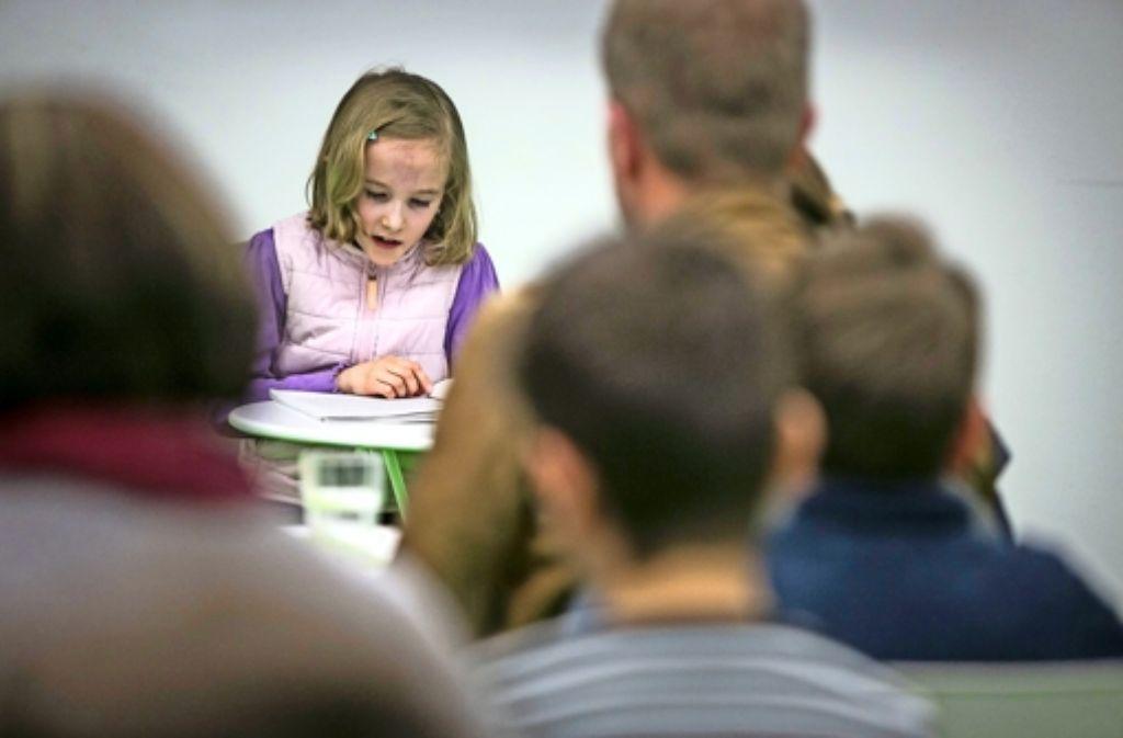 Gespannt hören die Lesungsbesucher zu, was ihnen das Mädchen aus seiner selbst geschrieben Geschichte vorliest. Foto: Michael Steinert
