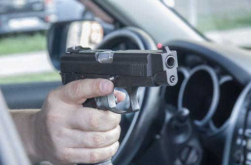 Mann zielt aus Auto heraus mit Luftpistole auf Gruppe