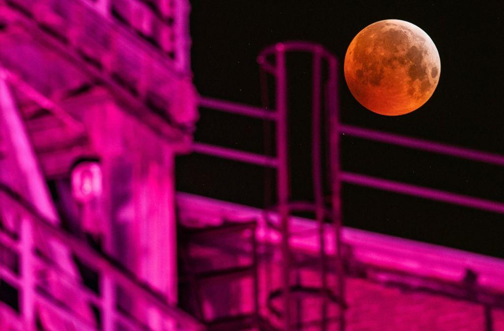 Ein angestrahlter Hochofen im Landschaftspark Duisburg setzt die Mondfinsternis besonders dramatisch in Szene. Foto: dpa