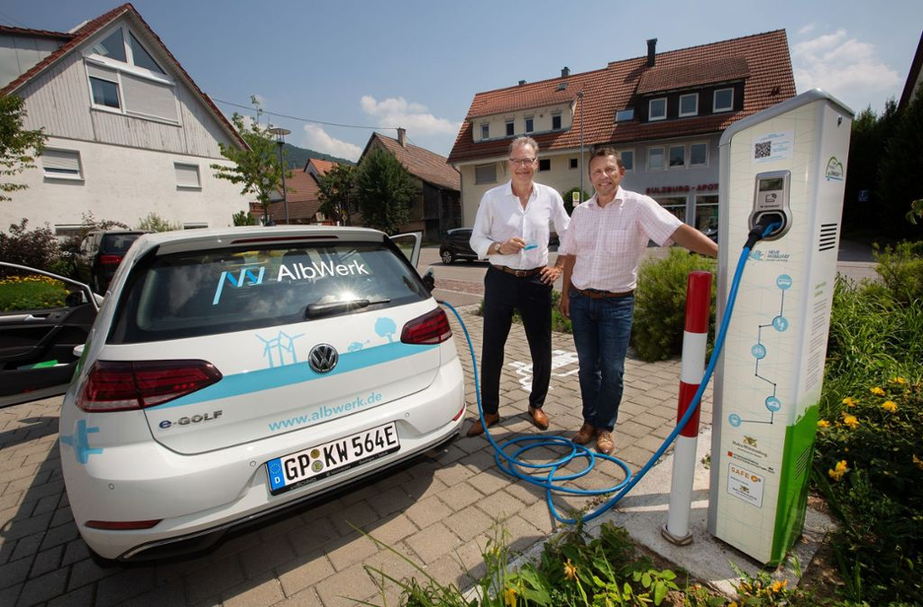 Der Lenninger Bürgermeister Michael Schlecht (rechts) und der EVL-Geschäftsführer Christian Gropp hängen das geliehene E-Mobil ans Kabel. Foto: Ines Rudel