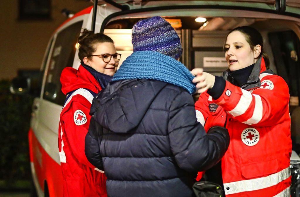 Sandra Welsch (r.) und Meriem Benyebka  geben einem Bedürftigen einen warmen Schal. Foto: Lichtgut/Christoph Schmidt