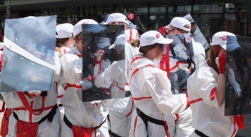 Die Teilnehmer der überwachungsfreien Tour tragen weiße Ganzkörperanzüge und ein verspiegeltes Schutzschild aus Plexiglas. Kameras können hier nicht hindurchsehen. Foto: Jan Georg Plavec