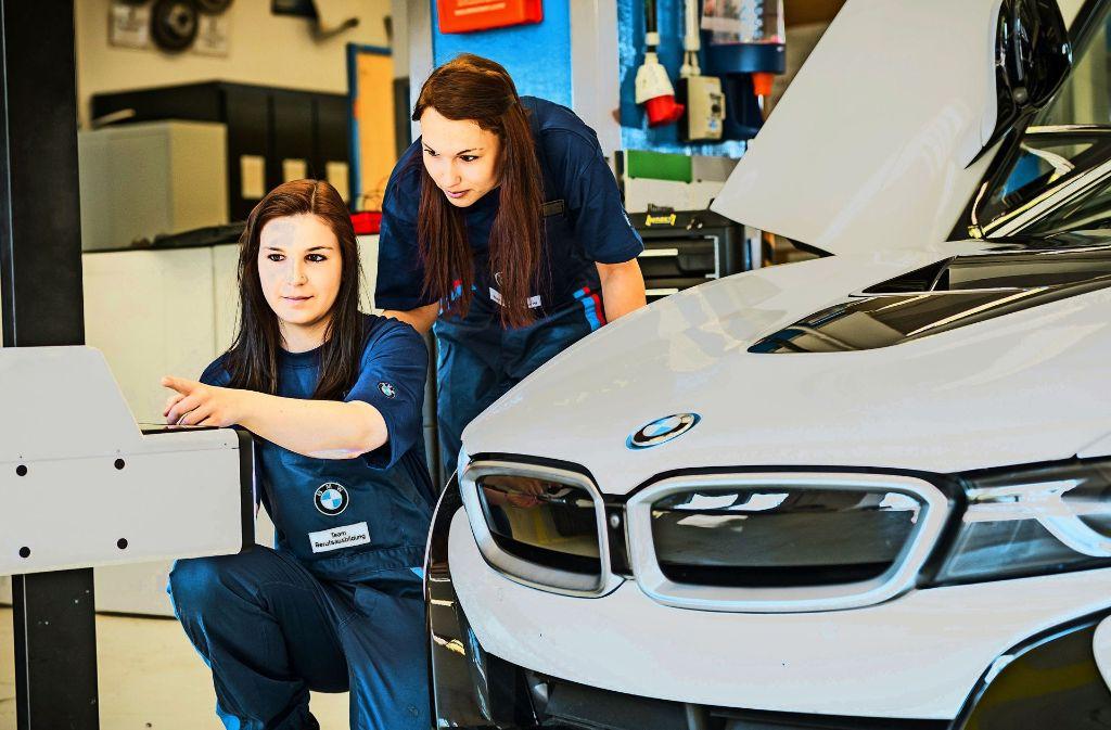Zwei Azubis arbeiten an einem BMW i8. Foto: BMW