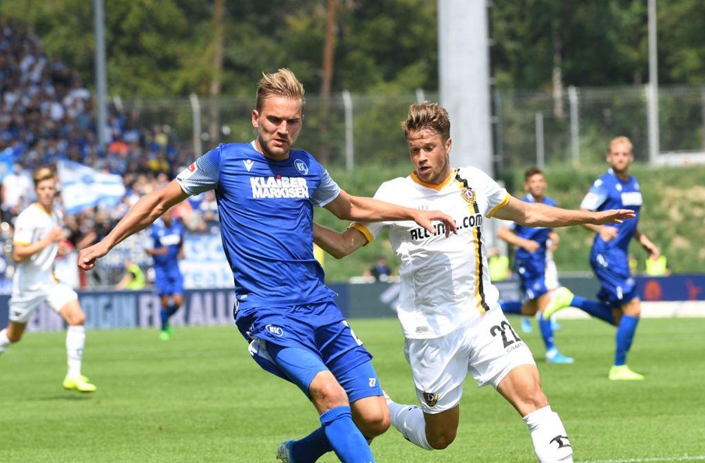 Der Karlsruher Lukas Grozurek (l) und der Dresdner Patrick Möschl kämpfen um den Ball. Foto: dpa