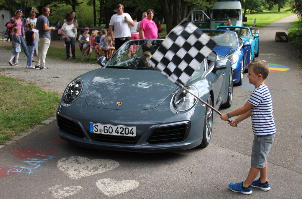 Der fünfjährige  Finn schwenkt die Startflagge, und gleich geht es los: Drei Porsche 911 Carrera mit zusammen mehr als 1000 PS setzen sich in Bewegung. Foto: Bernd Zeyer