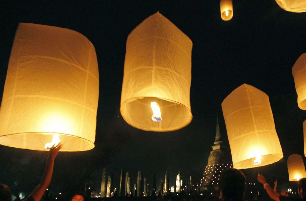 In Thailand werden sogenannte Himmelslaternen bei einem Fest angezündet, bevor sie in die Luft aufsteigen. Foto: dpa/Barbara Walton