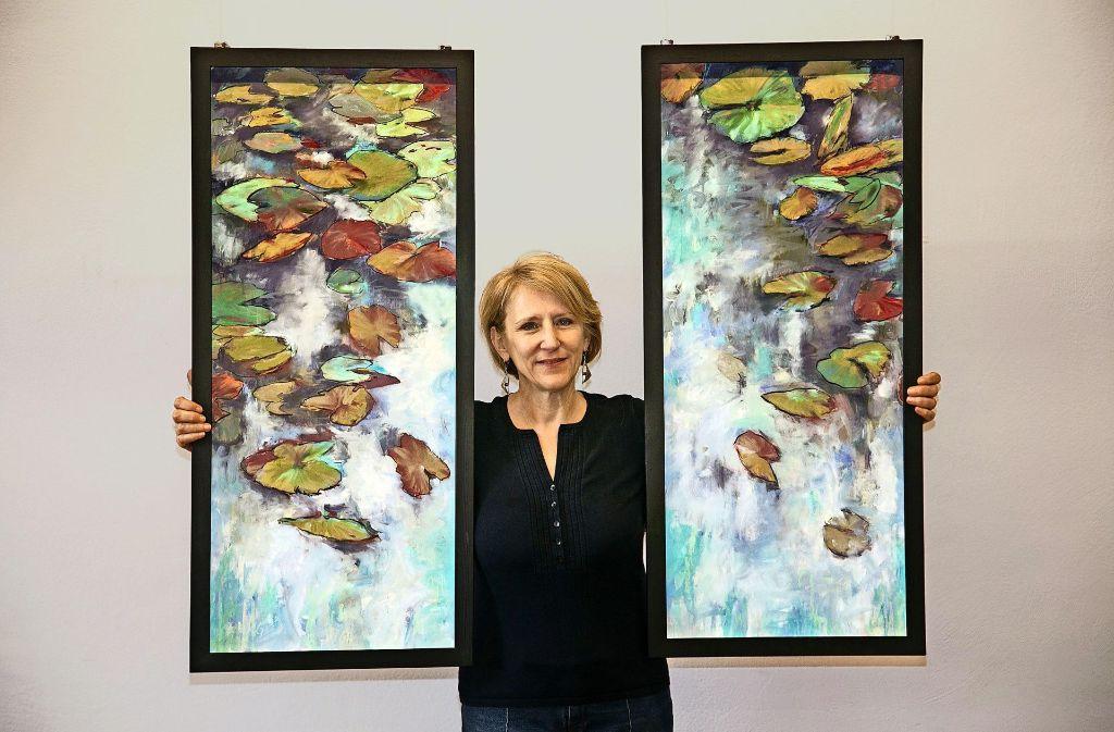 Die Geislinger Malerin Gabriele Glang umarmt  hier zwei ihrer Seerosenbilder. Foto: Ines Rudel