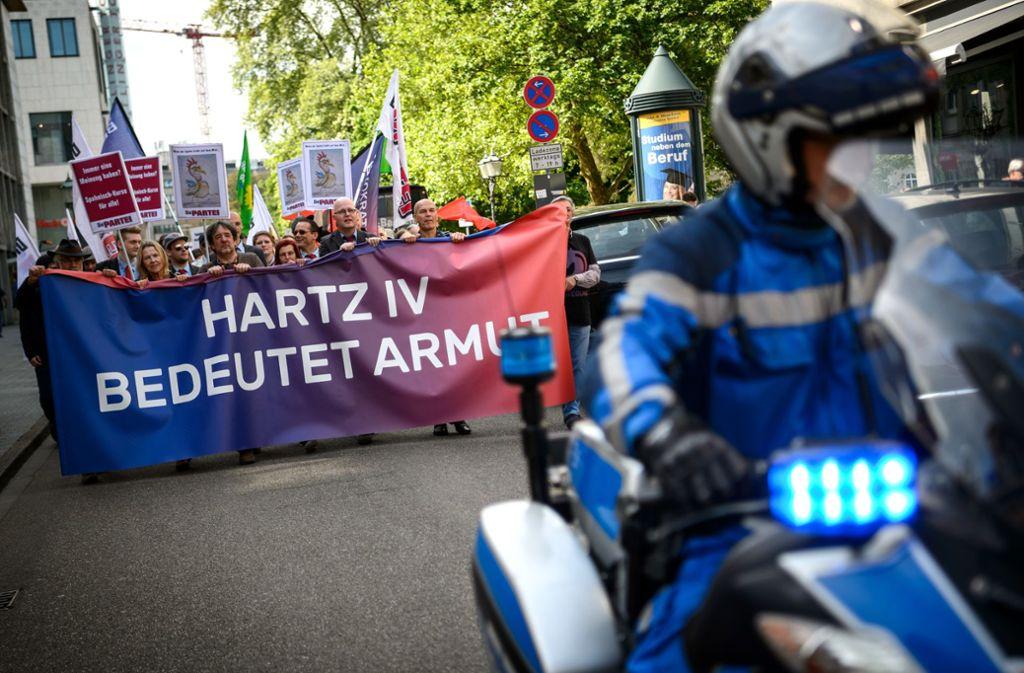 """28.04.2018, Baden-Württemberg, Karlsruhe: Demonstranten tragen ein Banner mit der Aufschrift """"Hartz IV bedeutet Armut"""" Foto: picture alliance / Sina Schuldt//Sina Schuldt"""