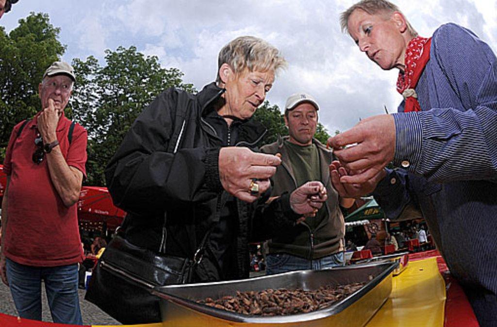 Ute Woyke zeigt auf dem Hamburger Fischmarkt, wie die Krabben aus der Schale kommen. Foto: HHT