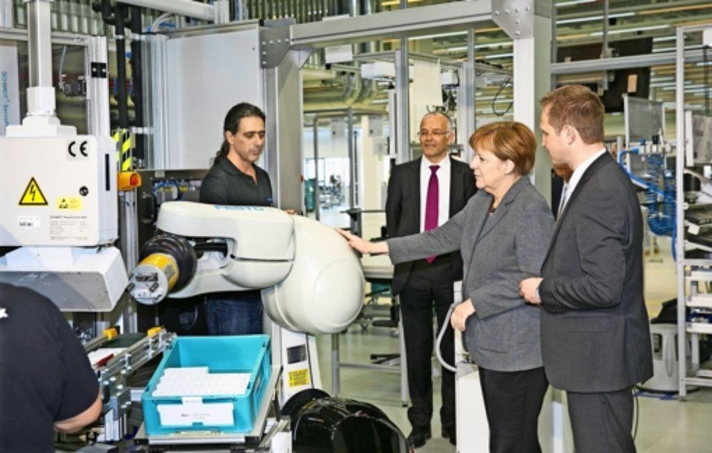 Eingerahmt vom Werksleiter Stefan Schwerdtle (rechts) und dem Vorstandsvorsitzenden von Festo, Claus Jessen, berührt Angela Merkel bei ihrem Rundgang durch die Fabrik Uschi –  den ersten Roboter, der keinen Käfig braucht. Foto: Horst Rudel