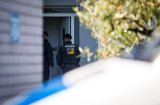 Polizeieinsatzkräfte in einer Straße in Rottenburg am Neckar (Baden-Württemberg) mit Anwohnern in der Nähe eines Gebäudes, das im Zusammenhang mit dem mutmaßlichen BVB-Attentäter durchsucht wurde. Foto: dpa