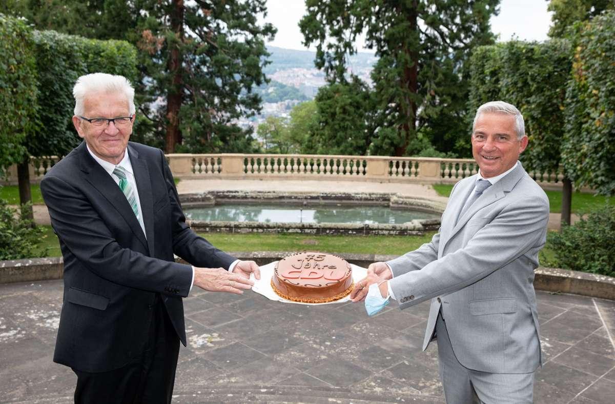 Winfried Kretschmann überreicht Thomas Strobl  eine Torte. Foto: dpa/Uli Regenscheidt