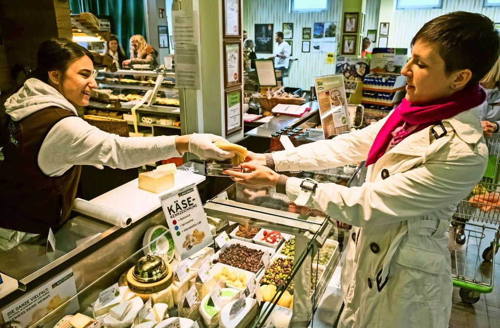 Anja Krisch (rechts) lässt sich in einem Naturkostladen den Käse in eine Metalldose legen, die sie  mitgebracht hat. Foto: Lichtgut/Achim Zweygarth