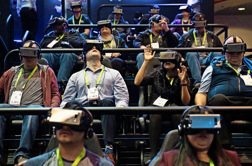 Was diese Menschen wohl sehen? Am Stand des Elektronikkonzerns Samsung probieren CES-Messebesucher  VR-Brillen aus. Foto: AP, dpa  (2)
