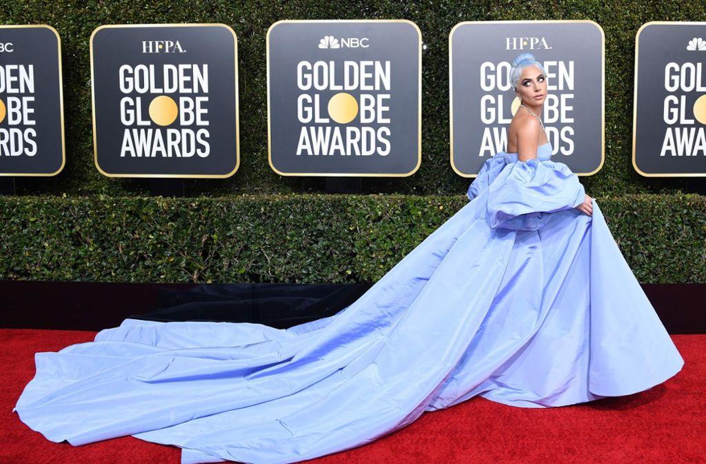 So kennen wir Lady Gaga: in einer überkandidelten eisblauen Robe von Valentino gewandet, schritt sie wie eine Rokoko-Dame über den roten Teppich. Passend dazu hat sie sich ihre Haare im selben Farbton gefärbt.    Foto: AFP