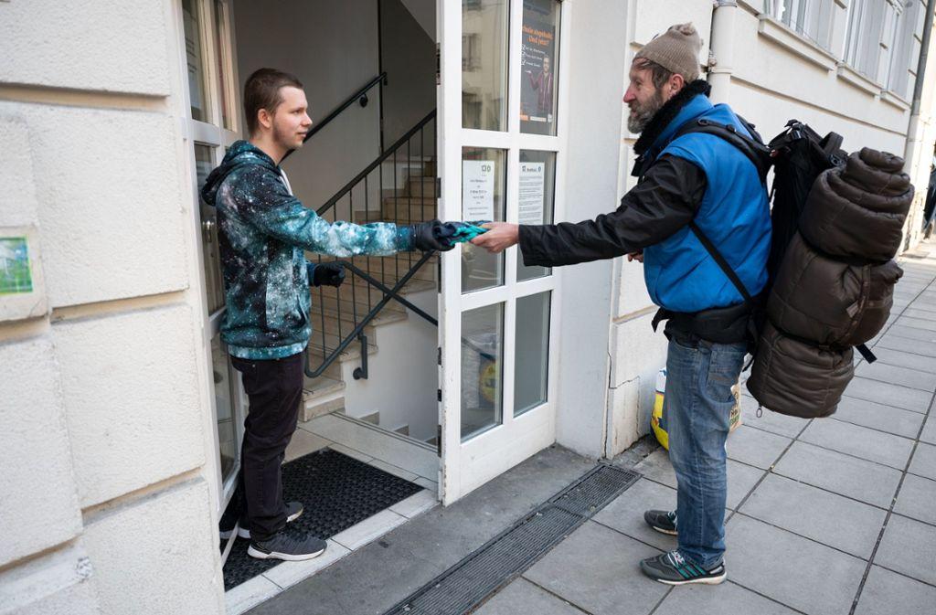 Ein Besucher der Obdachlosentagesstätte Olga 46 in Stuttgart erhält am Eingang Handschuhe. Foto: dpa/Marijan Murat