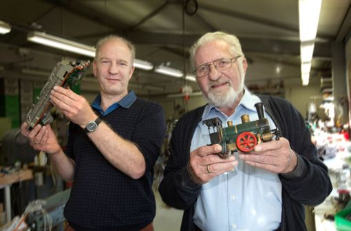 Vater und Sohn arbeiten mit Volldampf an Loks
