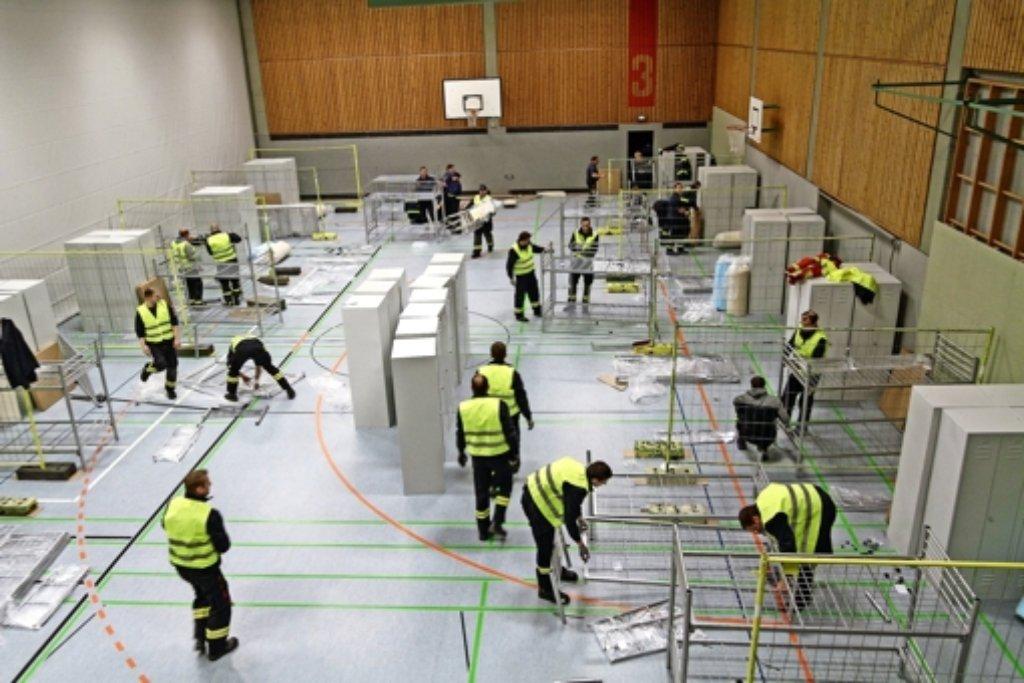 Innerhalb kürzester Zeit bauen die Helfer von Feuerwehr und THW die einzelnen Abteile und Stockbetten für die Flüchtlinge auf. Foto: factum/Bach