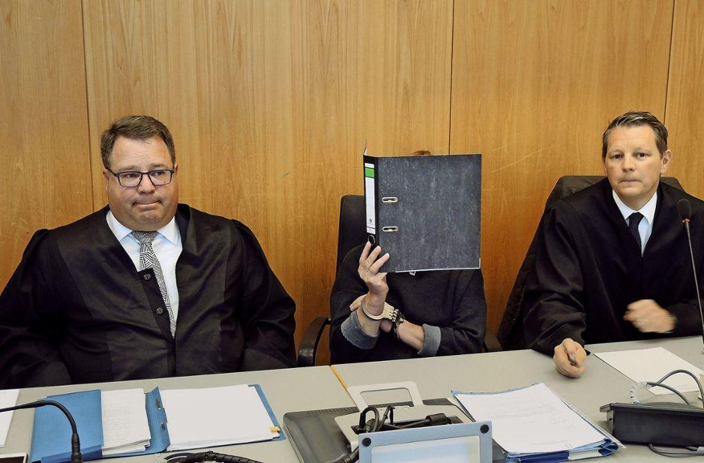 Die Angeklagte verbirgt vor Beginn der Verhandlung ihr Gesicht hinter einem Aktenordner. Rechts neben ihr Verteidiger Achim Wizemann, links Christian Fischer. Foto: dpa/Thomas Burmeister Foto: