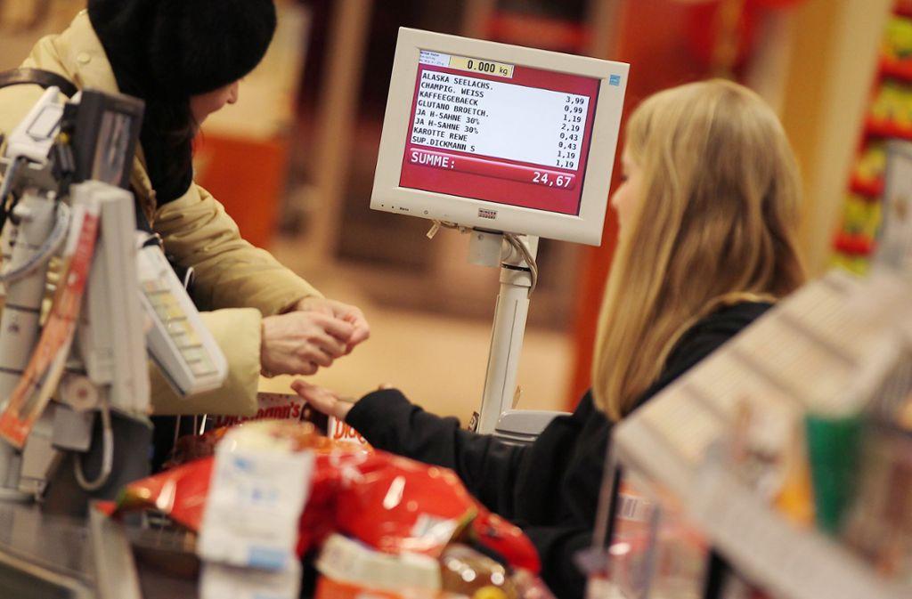 Praktisch ungeschützt vor Viren nimmt eine Kassierein in einem Supermarkt das Geld einer Kundin entgegen. Foto: /Oliver Berg