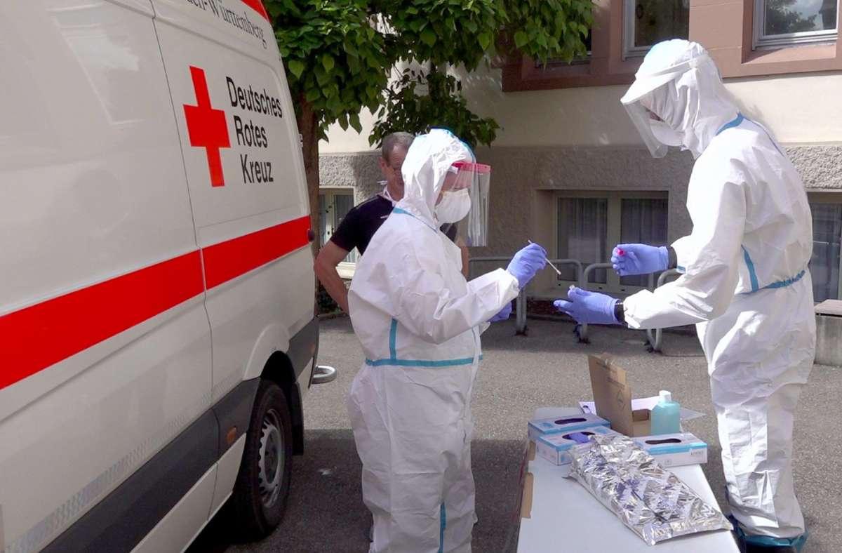 Mitarbeiter des Deutschen Roten Kreuzes testen im Schutzanzug an einer Schule in Göppingen. Foto: dpa/Alexander Wölfl