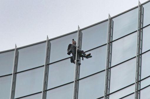 Französischer Kletterer hangelt sich an Hochhaus hoch