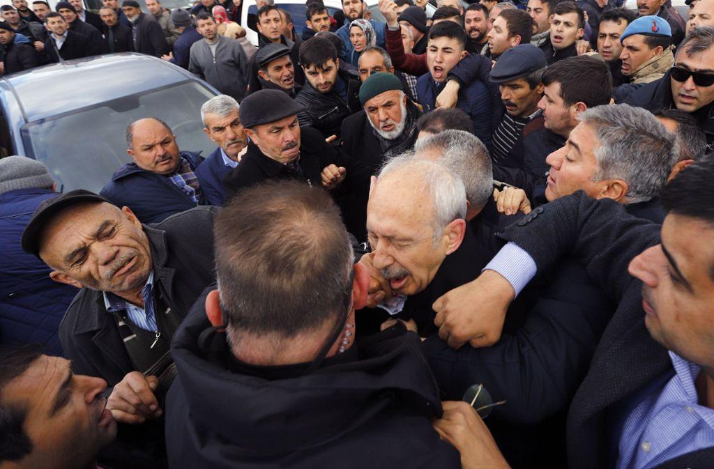 Ein Mann schlägt Kemal Kilicdaroglu (Mitte), Vorsitzender der kemalistisch-sozialdemokratischen CHP, mit der Faust ins Gesicht. Kilicdaroglu ist auf der Beerdigung eines Soldaten von einem Mob angegriffen worden. Foto: AP