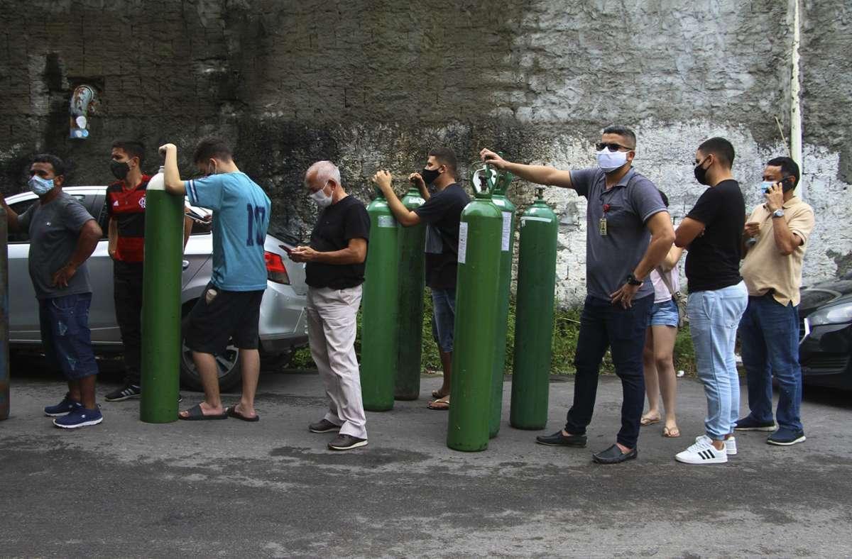 Familienmitglieder von Covid-19-Patienten stehen an, um Sauerstoffflaschen auffüllen zu lassen. In Manaus herrscht derzeit akuter Mangel von Sauerstoff für Kranke. Foto: dpa/Edmar Barros