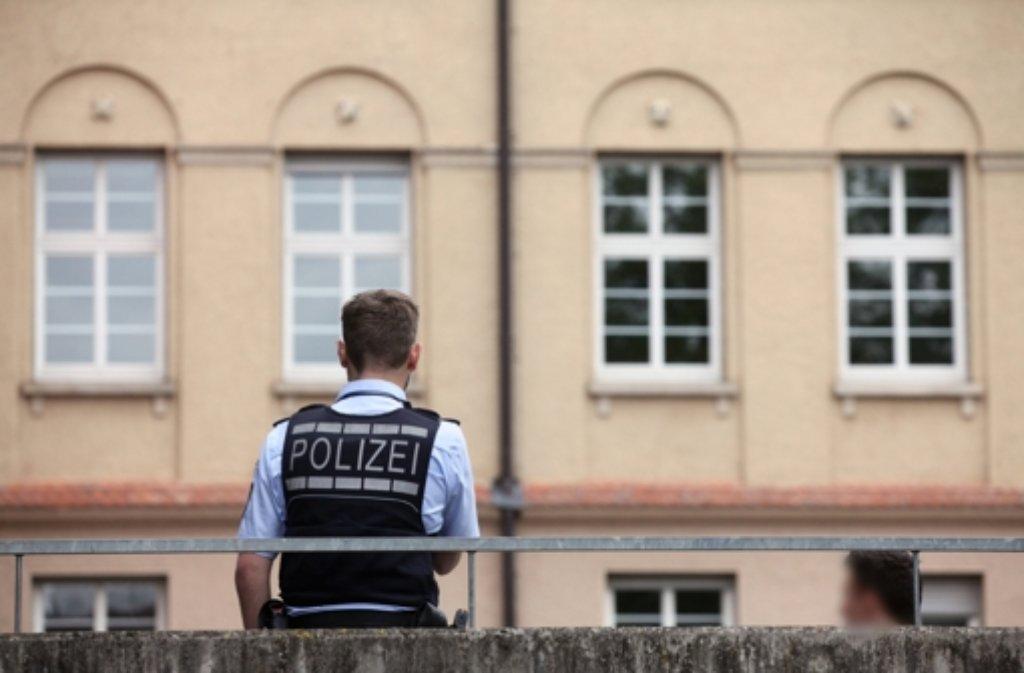 Ein Polizist steht in Nürtingen vor der Schule, in der ein Mädchen in der Toilette überfallen und gefesselt wurde. Foto: dpa