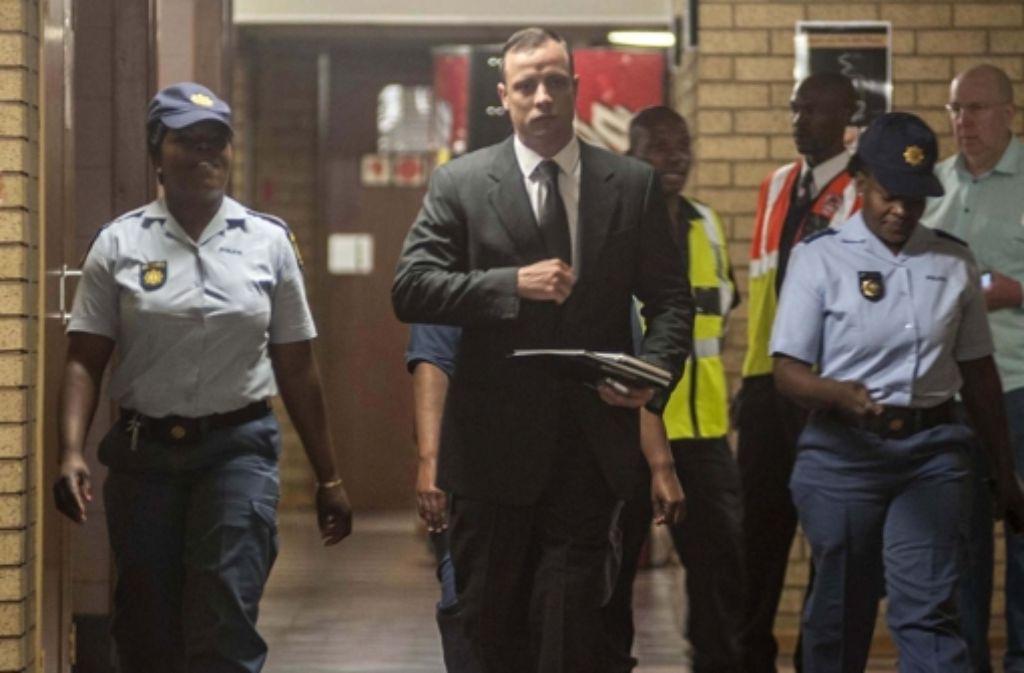 Oscar Pistorius auf dem Weg zum Gericht. Nach einem Jahr im Gefängnis wird er nun in den Hausarrest entlassen – vorerst. Foto: