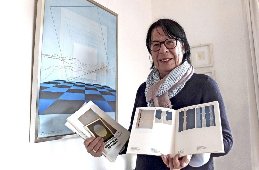Gabriele Frik-Heintschel mit Katalogen und Büchern vor einem Gemälde ihres Mannes Hermann Heintschel. Foto: Iris Frey