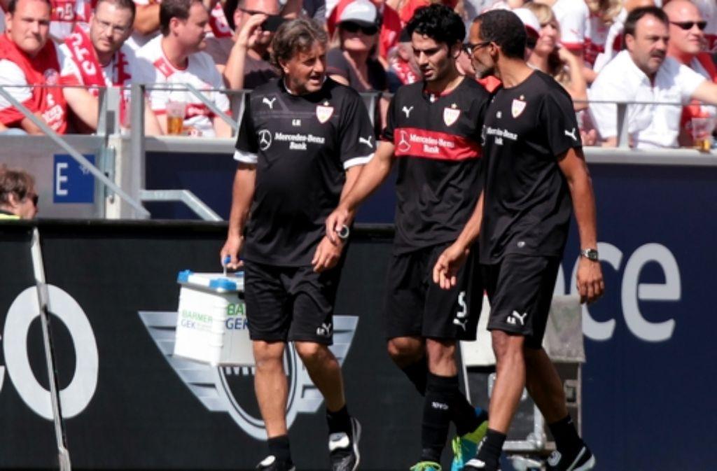 Vorzeitiges Dienstende in Mainz: der VfB-Kapitän Serdar Tasci (Mitte) wird vom Mannschaftsarzt Raymond Best (rechts) und dem Physiotherapeuten Gerhard Wörn vom platz geführt. Foto: Baumann