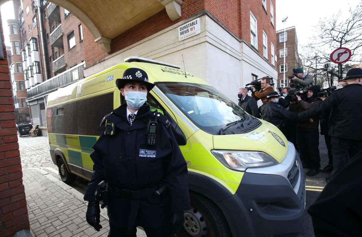 """Polizisten und Sicherheitskräfte machen den Weg frei für einen Krankenwagen, als dieser durch einen Hinterausgang das """"King Edward VII Krankenhaus"""" verlässt. Foto: dpa/Yui Mok"""