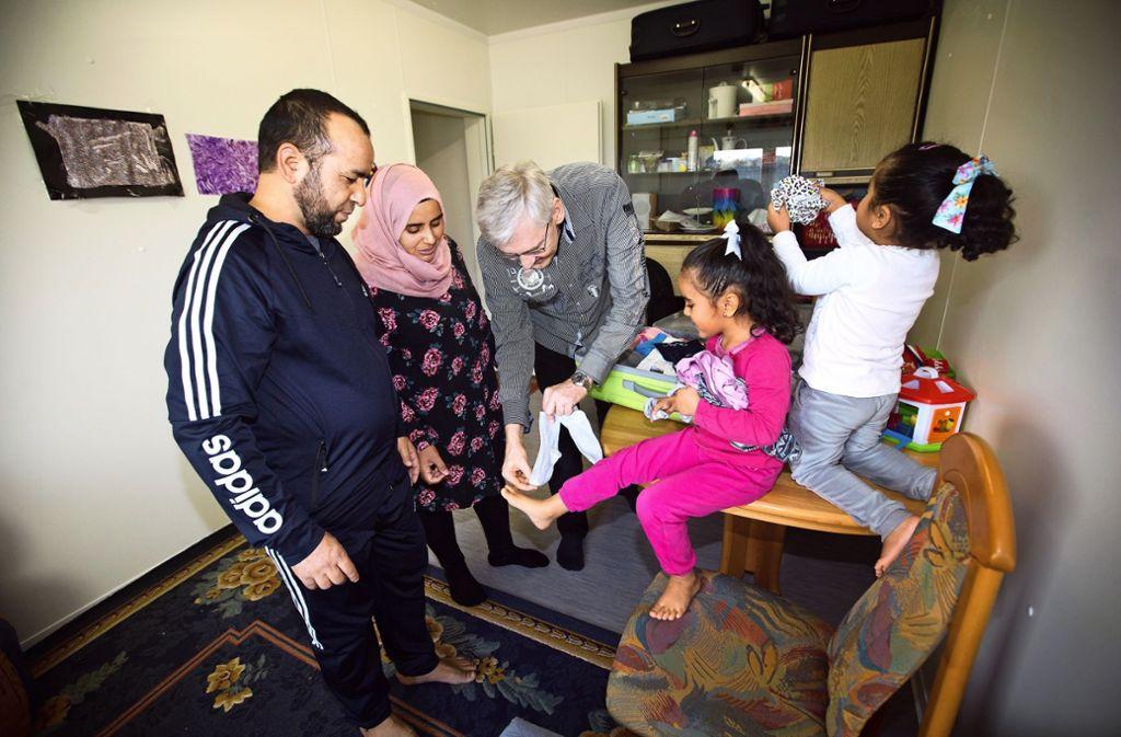 Die könnten passen: der Familienpate Thomas Borowski (Mitte) hat Socken und Wäsche für die beiden Mädchen mitgebracht. Foto: Ines Rudel