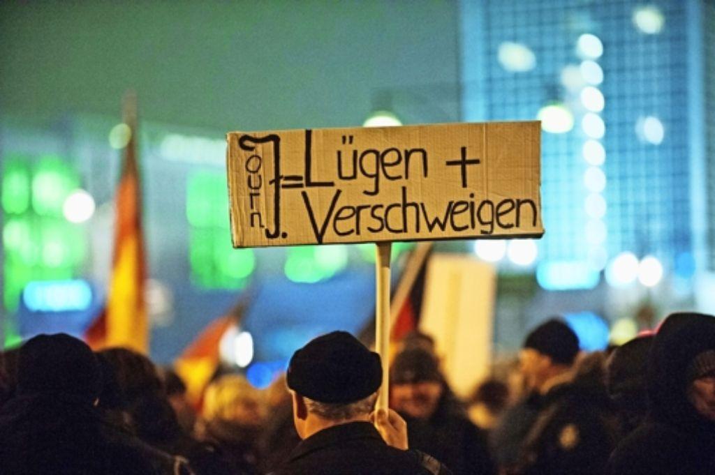 Auf einer Pegida-Demo in Berlin wird auf einem Plakat gegen Journalisten  gehetzt –  längst kommt es auch zu Handgreiflichkeiten und Schlägen gegen Filmteams oder Reporter. Foto: dpa