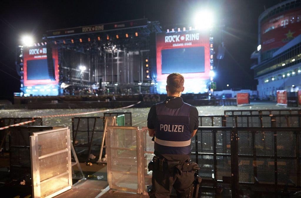 """Polizeibeamte durchsuchen nach dem Festivalabbruch wegen Terrorgefahr beim Musikfestival """"Rock am Ring"""" das Veranstaltungsgelände. Foto: dpa"""