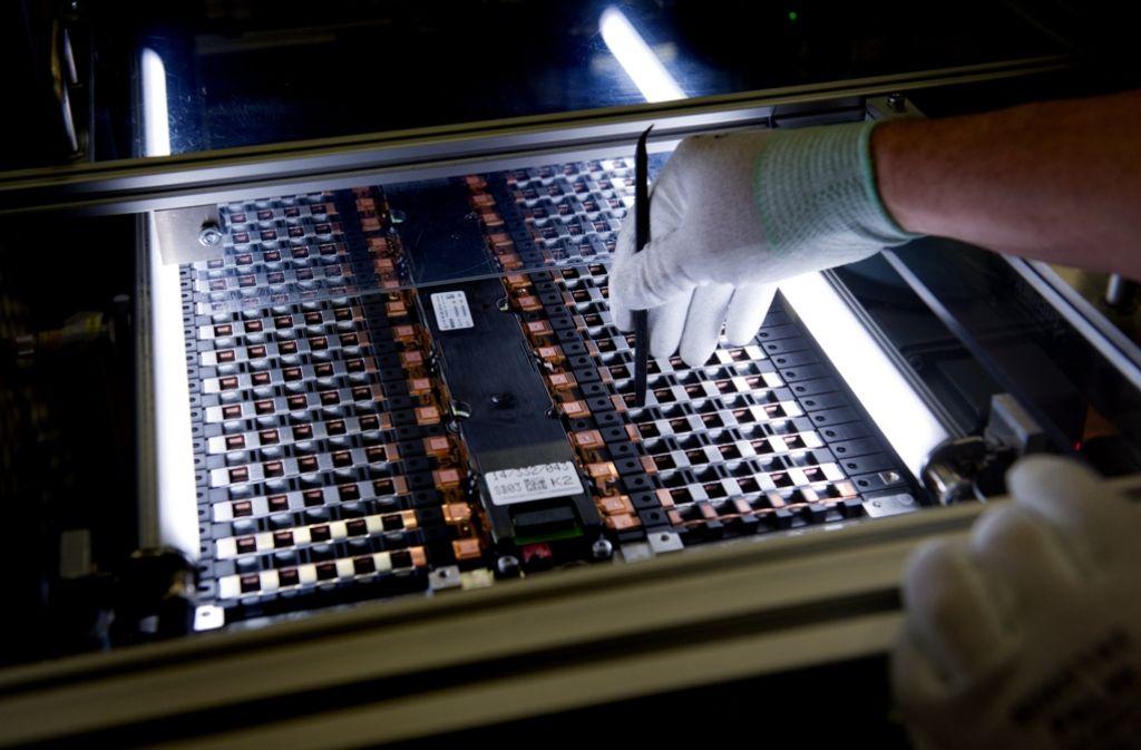 Ein Mitarbeiter der Daimler-Tochter Deutsche Accumotive arbeitet in der Produktion in Kamenz (Sachsen) an einer Zelle. Foto: dpa