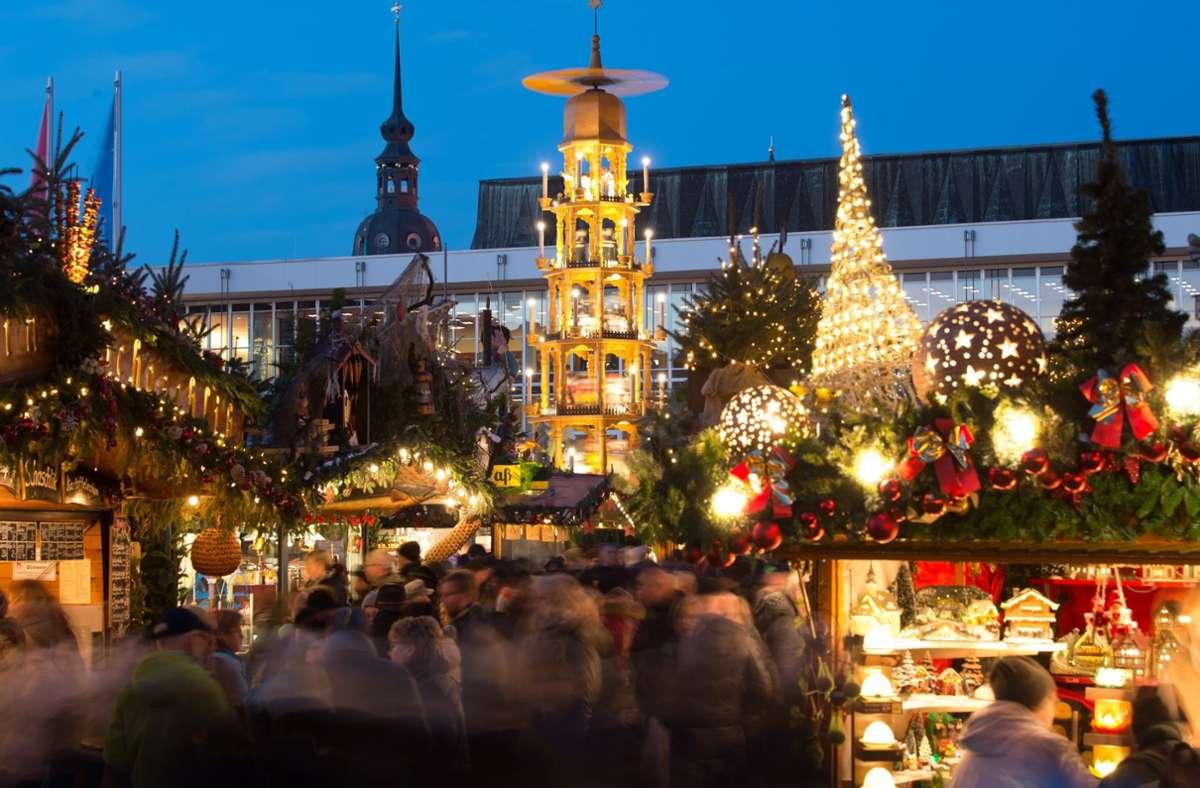 Die Weihnachtspyramide dreht sich hinter den Verkaufsständen auf dem Striezelmarkt. Foto: dpa/Sebastian Kahnert