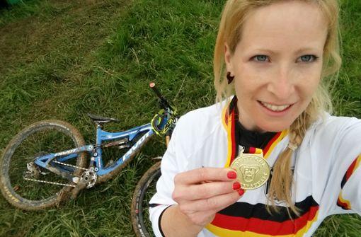 Vergoldetes Fahrkönnen bei der deutschen Meisterschaft! Bikerin Katrin Karhof hält stolz ihre Medaille in die Kamera.