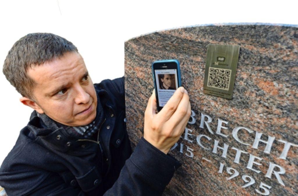 Der Bestatter Mark Ramsaier zeigt in Weilimdorf eine Trauerseite eines Verstorbenen. Die Trauerseite wird über einen QR-Code auf einem Grabstein angesteuert. Foto: dpa