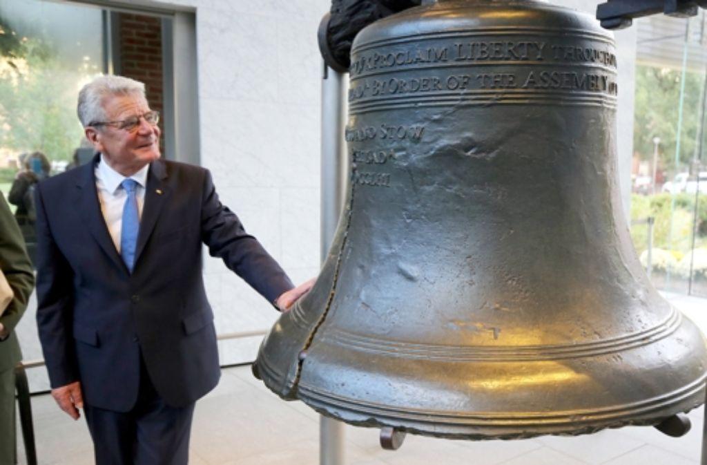 Bundespräsident Joachim Gauck berührt ergriffen die Freiheitsglocke. Foto: dpa