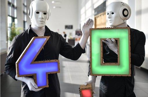 Die digitale Arbeitswelt – Stichwort Industrie 4.0 – verändert auch die Arbeitsweisen. darauf müssten die Unternehmen und die Politik reagieren, fordern die Grünen.  Im Bild zwei als Roboter verkleidete Darsteller  auf der Hannover Messe im April. Foto: dpa