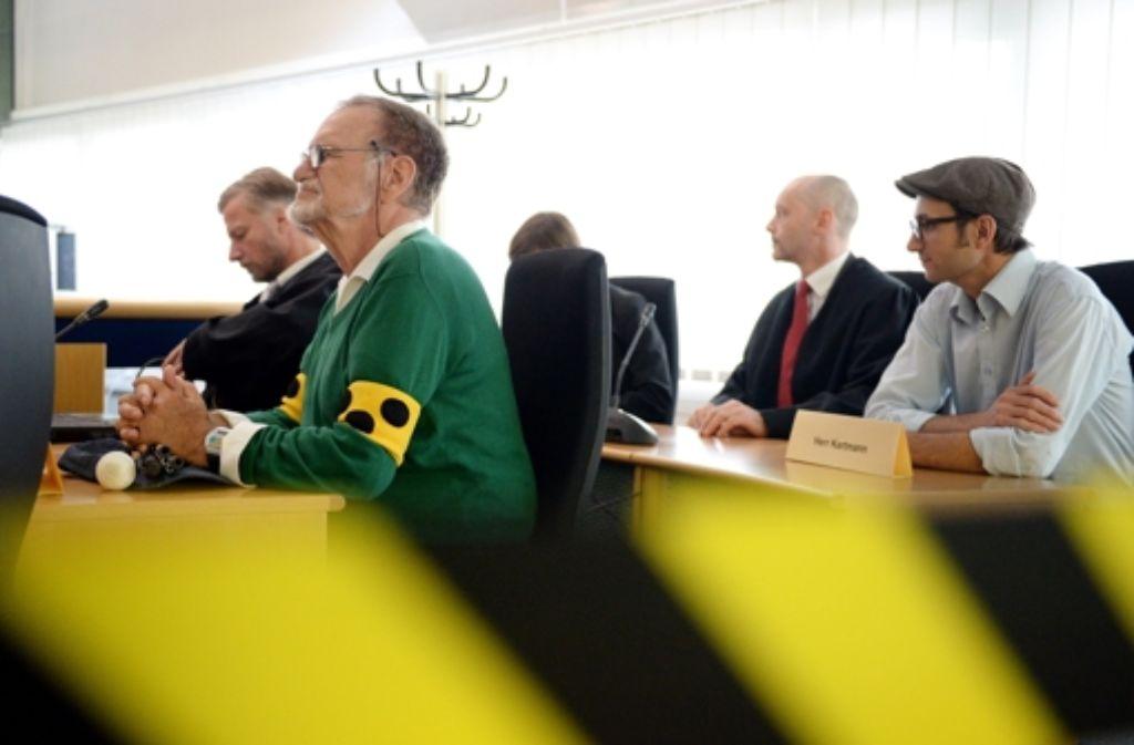 Dietrich Wagner (2.v.l), Nebenkläger im Wasserwerfer-Prozess, sitzt im Juni 2014 zusammen mit dem Anwalt Frank-Ulrich Mann (links) beim Beginn des Wasserwerferprozesses im Gerichtssaal. Am Mittwoch könnte das Verfahren eingestellt werden. Foto: dpa