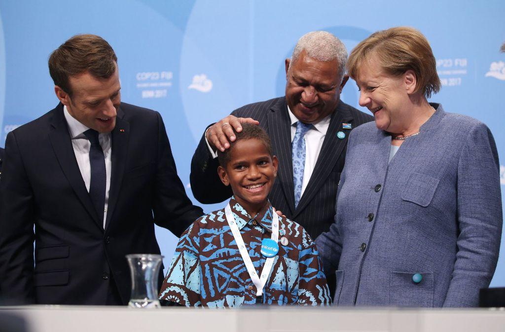 Angela Merkel und der französische Präsident Emmanuel Macron (links)  begrüßen bei der Weltklimakonferenz gemeinsam mit dem Premierminister der Fidschi-Inseln, Frank Bainimarama, einen zwölfjährigen Junge von den Fidschi-Inseln. Foto: dpa